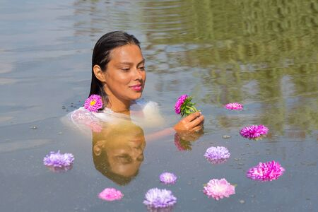 Portrait of colombian woman in water with  colorful flowers Фото со стока - 131026846