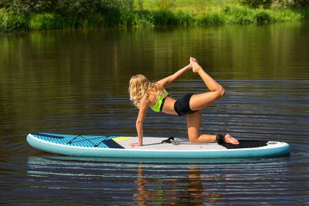 Young caucasian woman on SUP in yoaga pose on river