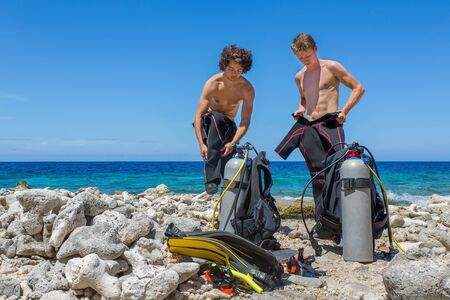 Two dutch divers changing clothes at the beach on Bonaire with blue sea Фото со стока