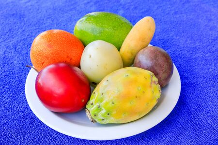 Dish with colorful special fruit on dish with blue background Фото со стока - 131026893