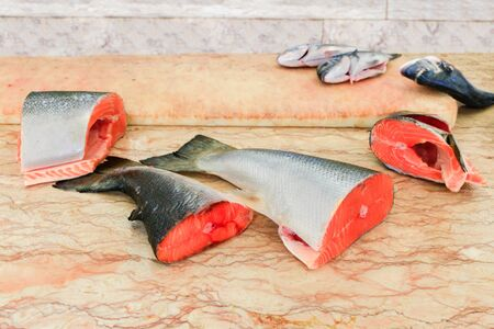 Pieces of cut fresh  salmon fishes lying  on marble table Фото со стока - 131026902