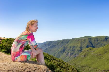 Caucasian woman sits on portuguese mountain near green valley Фото со стока - 131026903