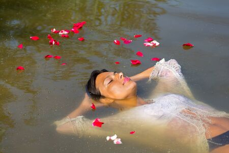 Colombian woman floating in natural water with rose petals Фото со стока - 131026905