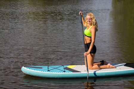 Kneeling young dutch woman paddles with SUP on water of lake