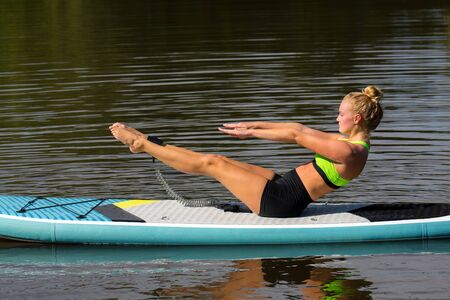 Young woman in yoga posture on SUP on water surface Фото со стока