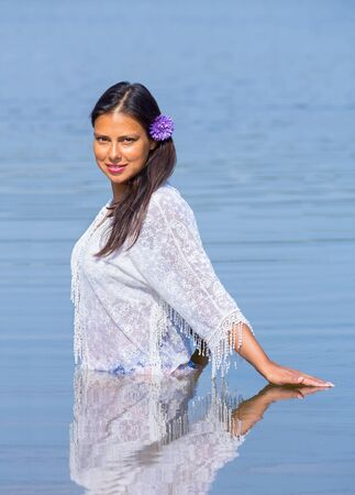 Colombian woman with black hair and white clothes stands in natural water Фото со стока