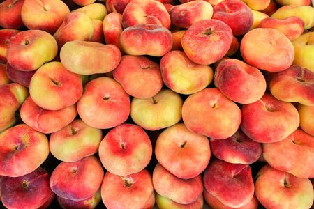 Multiple colorful fresh flat peaches for sale at market