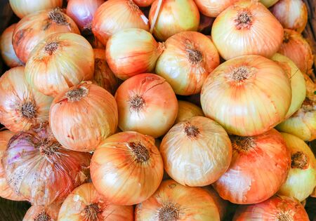 Many yellow orange onions for sale as vegetable at market Фото со стока - 131026939