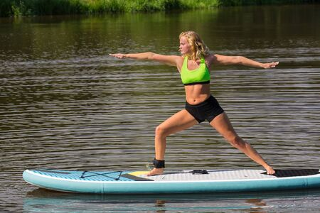 Young european woman on SUP in yoga posture on pond Stock Photo