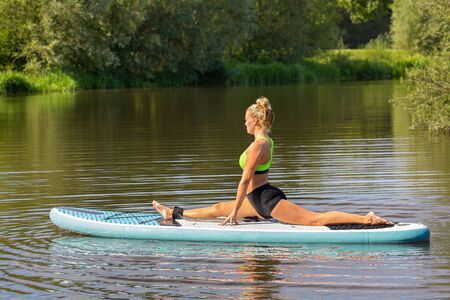 Young european woman in yoga posture on SUP in water