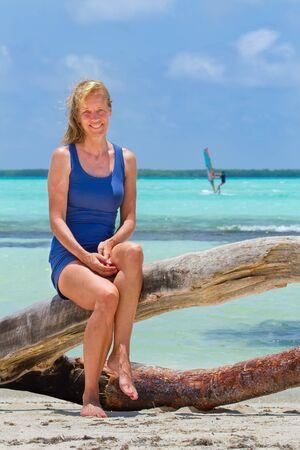 Caucasian woman sitting on tree trunk at Sorobon beach on Bonaire Фото со стока - 131026973