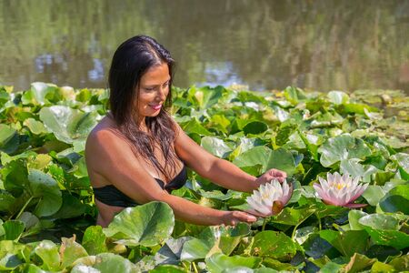 Colombian woman holding water lily in natural water of dutch pond Фото со стока - 131026975