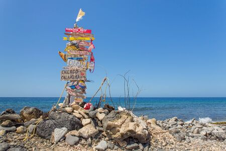 Signpost with stones at beach with sea of Bonaire Фото со стока - 131026977