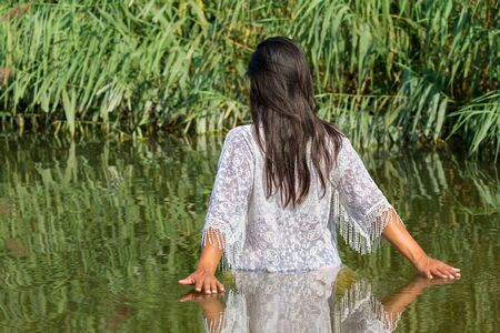 Colombian woman with black hair and white clothes walks in natural water