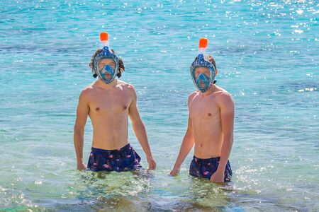 Two young caucasian men wearing snorkel masks in sea