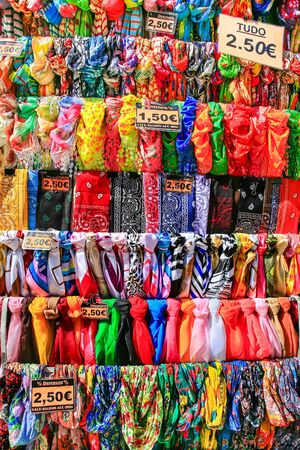 Rows with many colorful scarves hanging for sale at market place