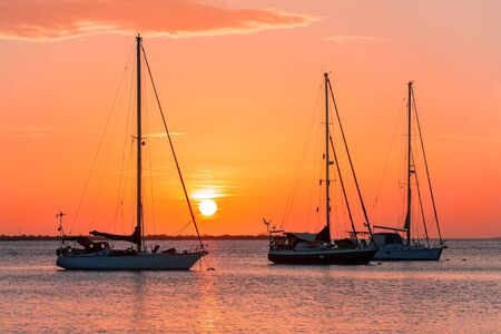 Three sailing boats together on sea at setting sun