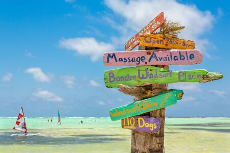 Colorful signpost at coast of Bonaire with windsurfers on sea