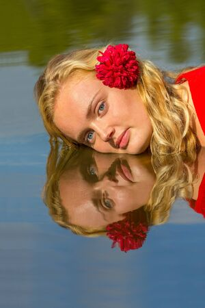 Portrait of young dutch woman with head reflectiing in water Standard-Bild - 131027140