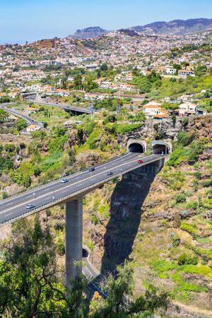 Cars driving on highway and overpass with two  tunnels at Madeira in country Portugal Standard-Bild - 131027144
