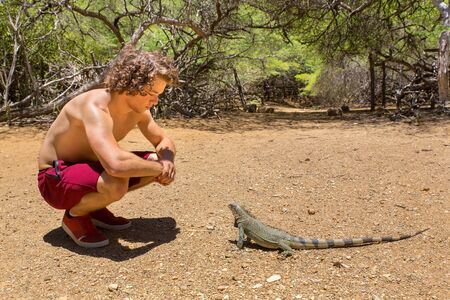 Young man sitting with green iguana in nature