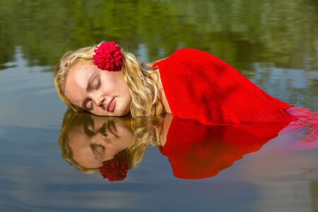 Portrait of young caucasian woman with reflection in natural water