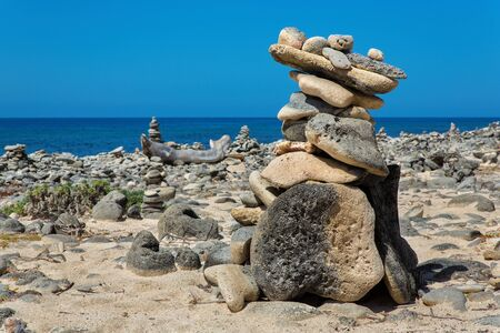 Pile of boulders on beach of bonaire with sea
