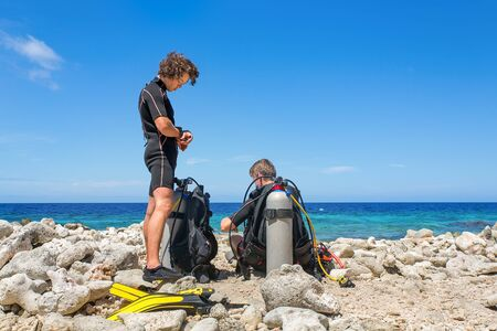 Two young dutch divers on the beach preparing for a dive at Bonaire