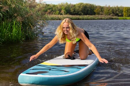 Young caucasian woman sailing with SUP board on water of european river