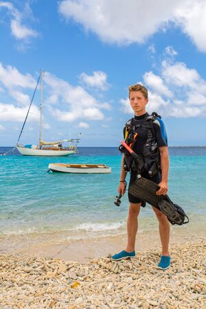 European male diver standing on beach of Bonaire with sea and boats
