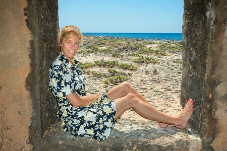 Caucasian woman sitting in window frame near sea on island Bonaire