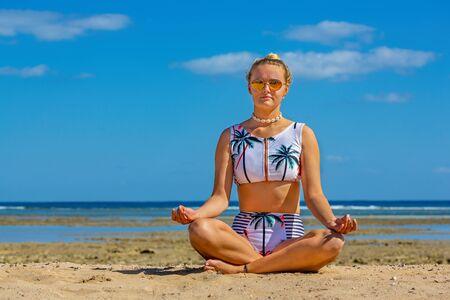 Young caucasian  woman in bikini meditates on beach with sea