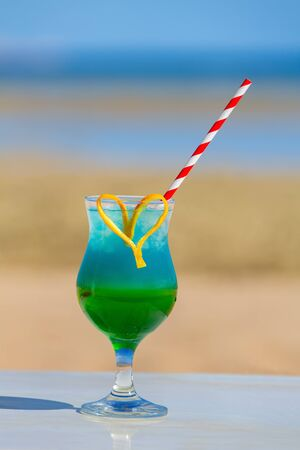 Colorful cocktail drink in glass at beach on sunny day Reklamní fotografie