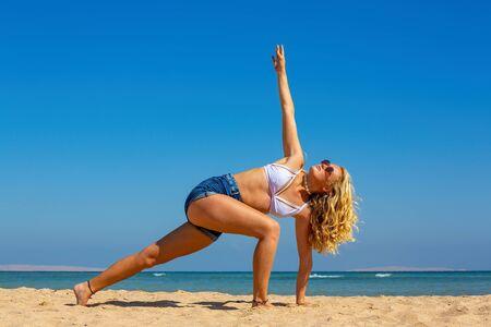 Young blonde dutch woman training yoga pose on beach near sea Standard-Bild