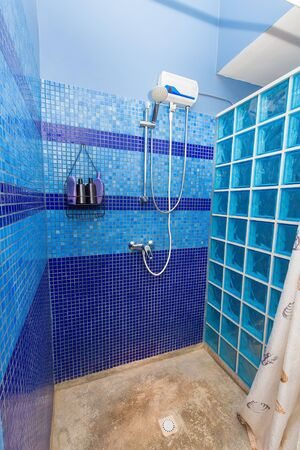 Shower cabin with blue wall tiles in apartment on Bonaire