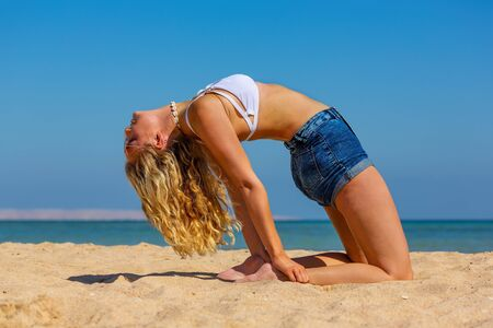 Young caucasian woman in back bend position on egyptian beach near blue sea Stock Photo