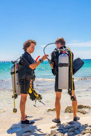 Two young caucasian divers checking diving equipment at coast of island Bonaire