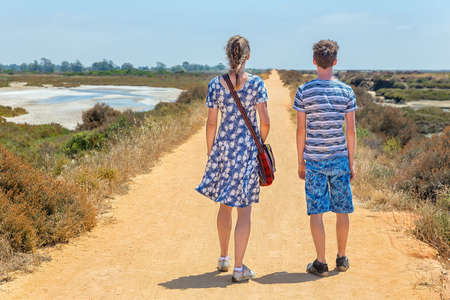 Woman and boy hiking on sandy path in portuguese coastal area