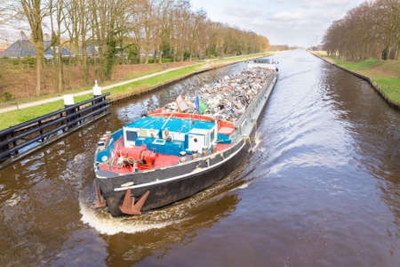 Dutch cargo ship sailing with recyclable metal on channel