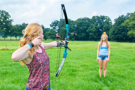 Dutch teenage girl aiming arrow of compound bow at fruit on head of young woman