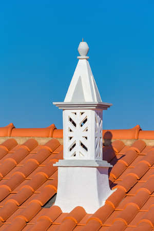 Graceful white chimney with orange roof tiles and blue sky Reklamní fotografie
