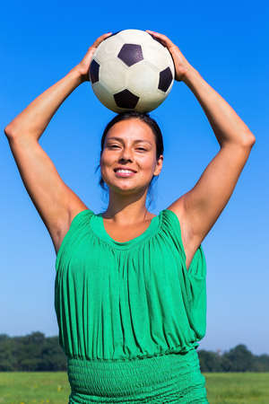 Young Colombian woman holding football on head in blue sky