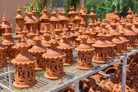 Many orange clay pots on rack outdoors at pottery shop