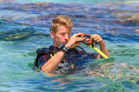 Young caucasian man as diver in sea preparing diving mask Reklamní fotografie