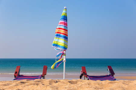 Colorful beach umbrella with chairs on beach with blue sea Reklamní fotografie