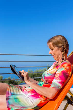 Middle aged caucasian woman sits on lounger reading tablet near sea