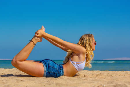 Young blonde caucasian woman bends backward on egyptian beach Reklamní fotografie