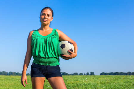 Standing young colombian woman holding football in front of blue sky Reklamní fotografie