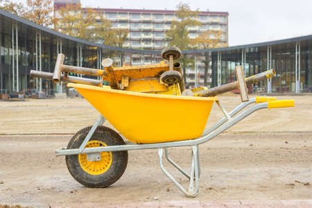Yellow wheelbarrow with stone cutter on new square pavement