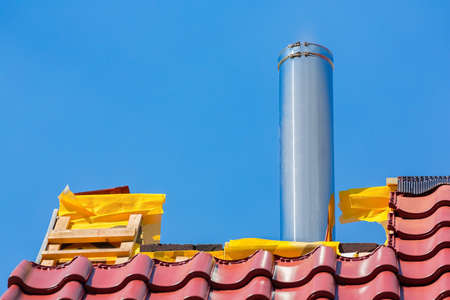 New roof with roof tiles and stainless metal chimney pipe against blue sky